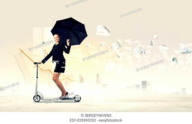 Image of young businesswoman in black riding scooter