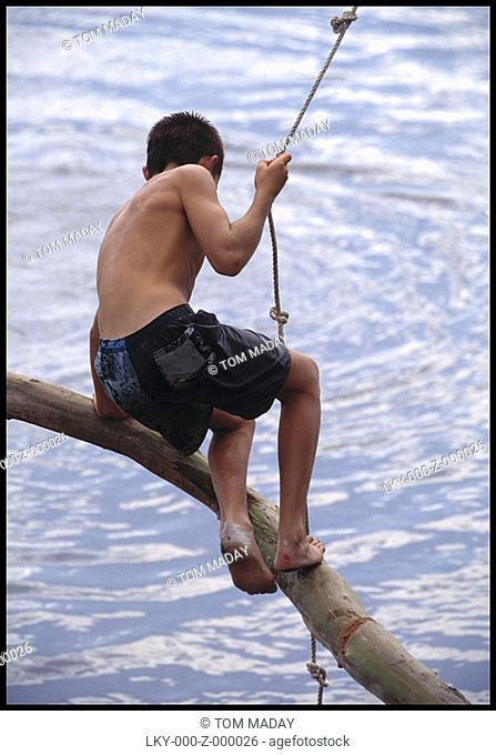 Boy ready to swing into river