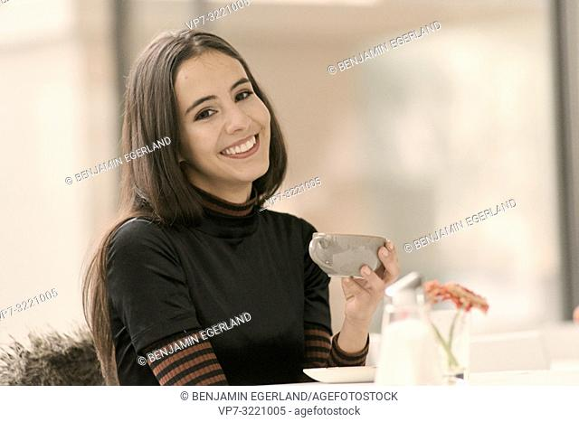 portrait of happy woman holding coffee cup while enjoying break at table in café, toothy smile, in Munich, Germany