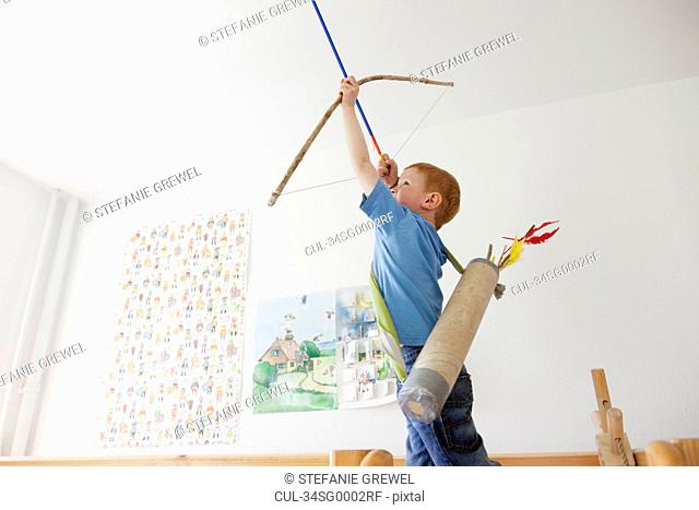 Boy playing with toy bow and arrow