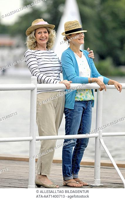 Mother and daughter standing on a landing stage