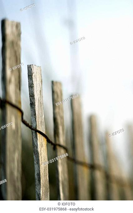 Image of wooden fence with rusted wiring