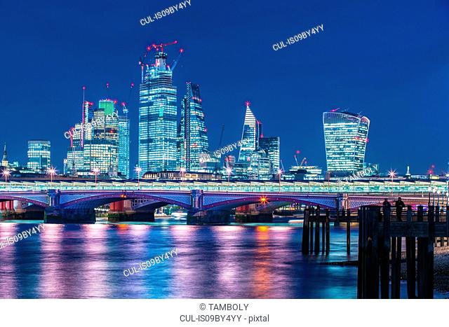 Skyline of financial district at night, Thames river on foreground, City of London, UK