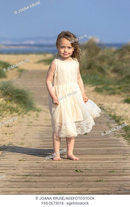 a 3 year old girl is standing on a boardwalk at the beach