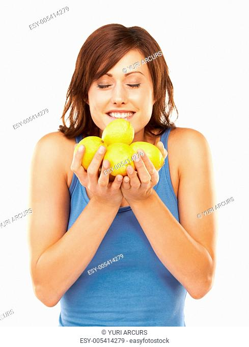 Studio portrait of a young woman holding a bunch of lemons up to her face isolated on white