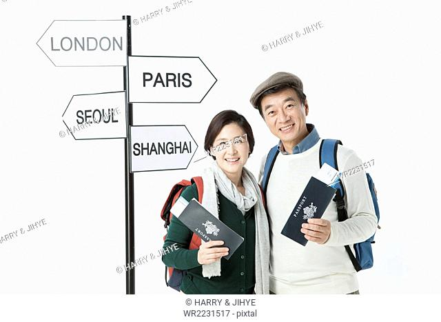 Middle aged traveling couple holding a passport and flight ticket each and staring forward with a smile next to the direction sign