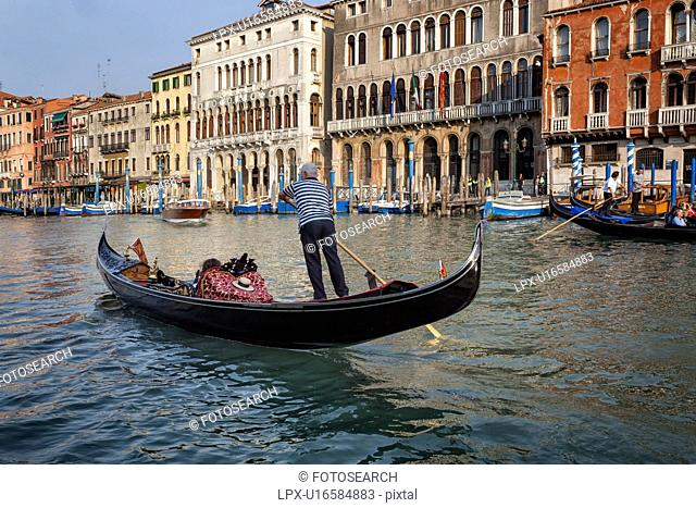 Grand Canal: gondolier rowing single passenger in foreground, ornately decorated palazzi, brightly coloured poles for mooring gondolas