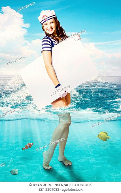 Fine art advertising of beautiful Australian sailor pin-up woman standing in ocean waves holding large blank sign board. Nautical copy space