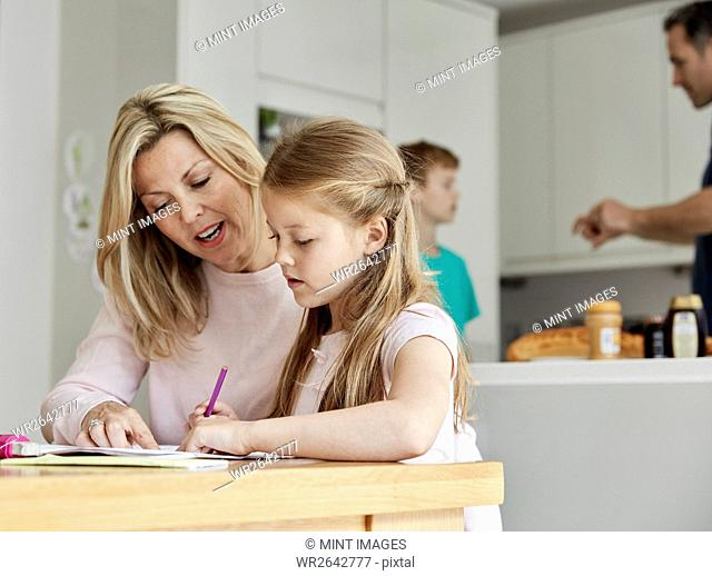 a woman and her daughter seated at a table in the kitchen looking at her homework