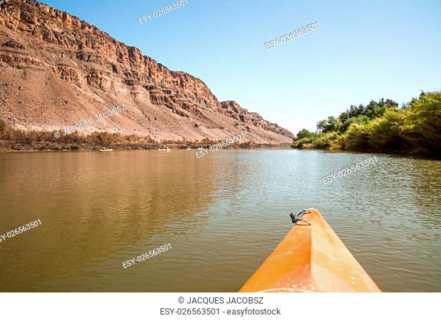 The nose of a kayak is in the foreground as people kayak along the Orange River on the border of South Africa and Namibia