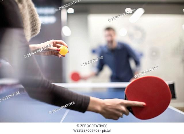 Two colleagues playing table tennis in office break room
