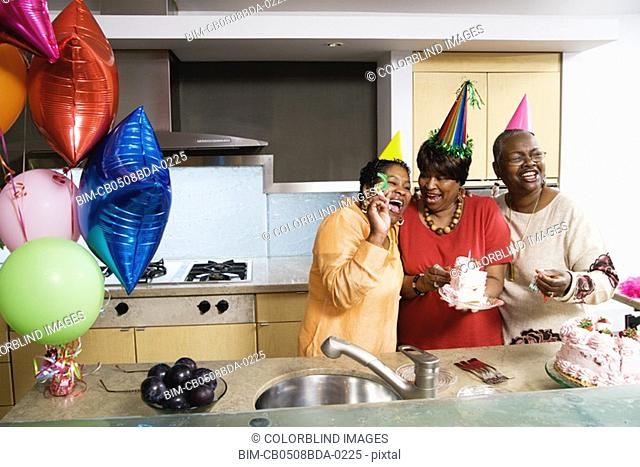 Three middle-aged African women at birthday party