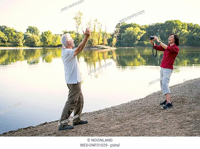 Happy senior couple at a lake taking pictures