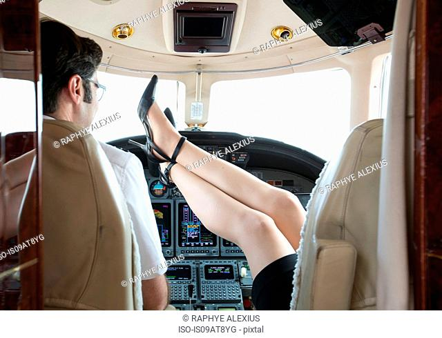 Rear view of female pilot with feet up in cockpit of private jet