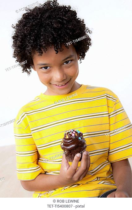 Studio portrait of boy 8-9 holding muffin