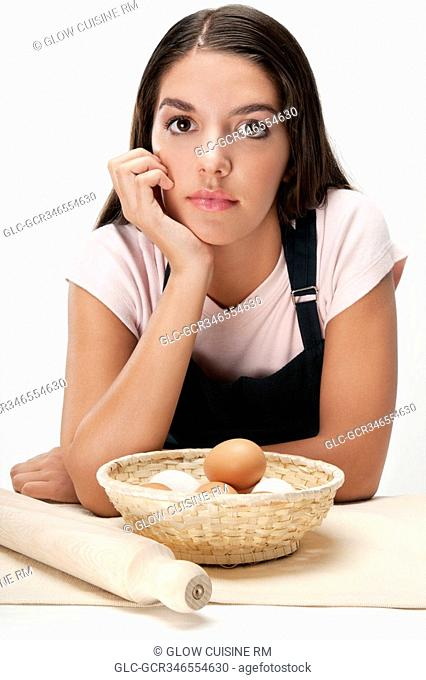 Woman thinking with a basket of eggs and a rolling pin