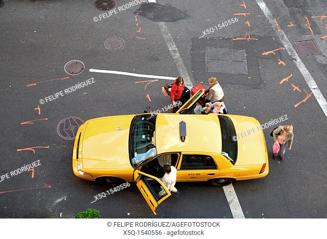 People getting in a yellow cab on 27th street, New York, USA