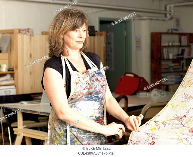 Woman checking fabric in hand-printed textile workshop