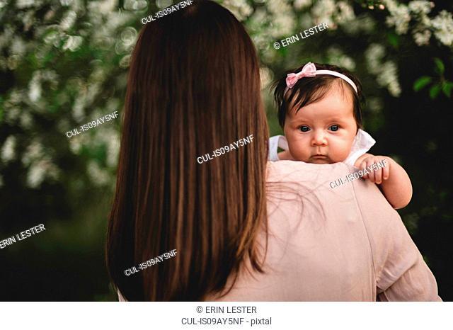Over shoulder portrait baby girl in mothers arms in garden