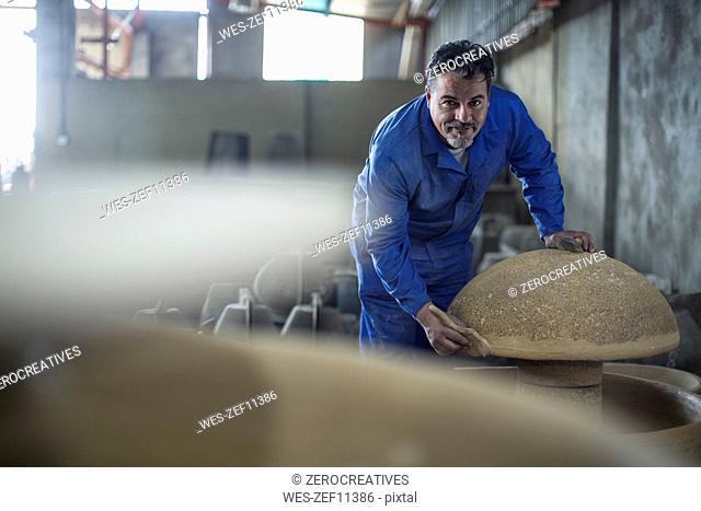 Portrait of confident worker in industrial pot factory