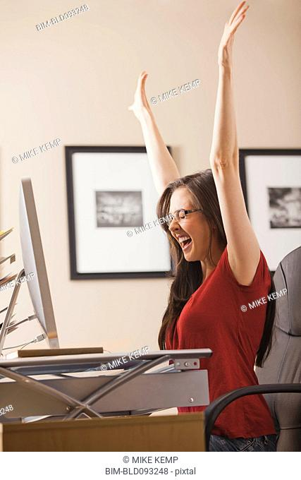 Caucasian woman cheering at desk in home office
