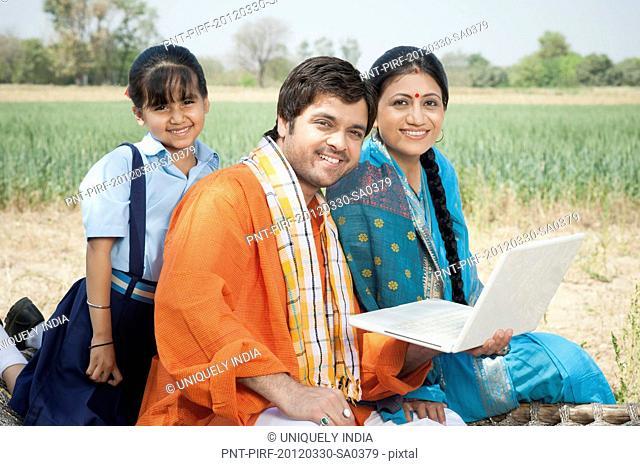 Farmer family using a laptop, Sohna, Haryana, India