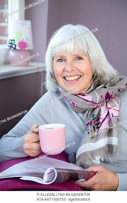 Elderly woman with coffee and magazine