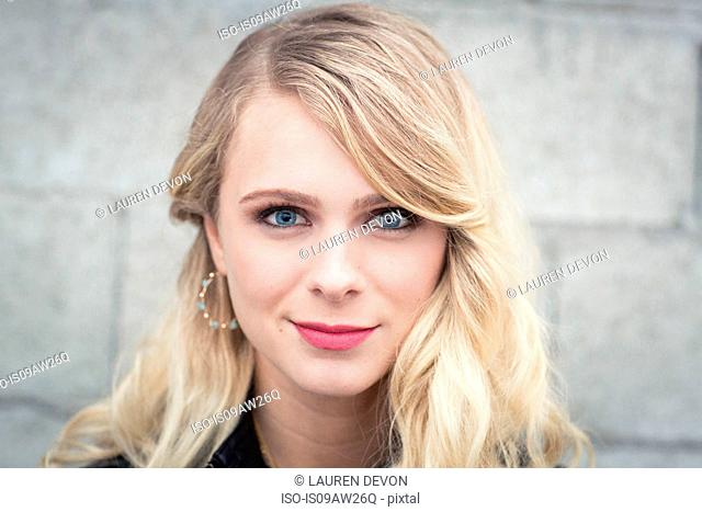 Young blonde haired woman in front of breeze block wall looking at camera smiling