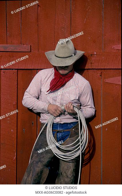 Cowboy standing against red barn, holding coil of rope