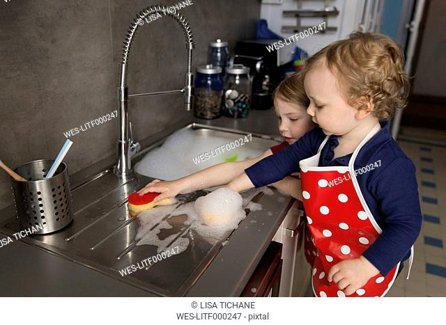 Little boy and girl cleaning sink with a sponge
