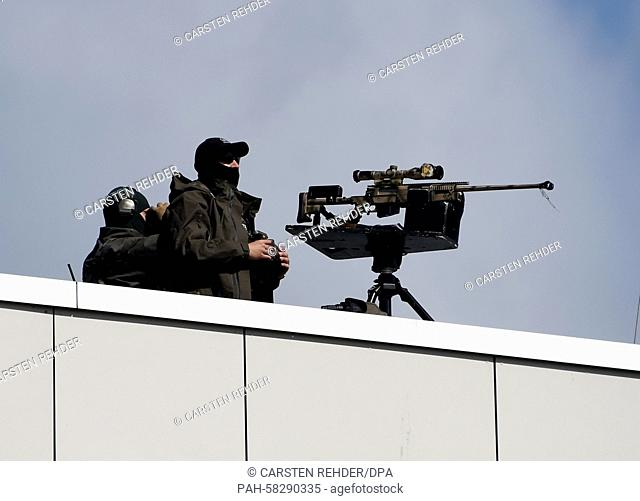 A police marksmen sits on a roof top as he secures the perimeter during the visit of Israeli President Reuven Rivlin (not in picture) in Kiel, Germany