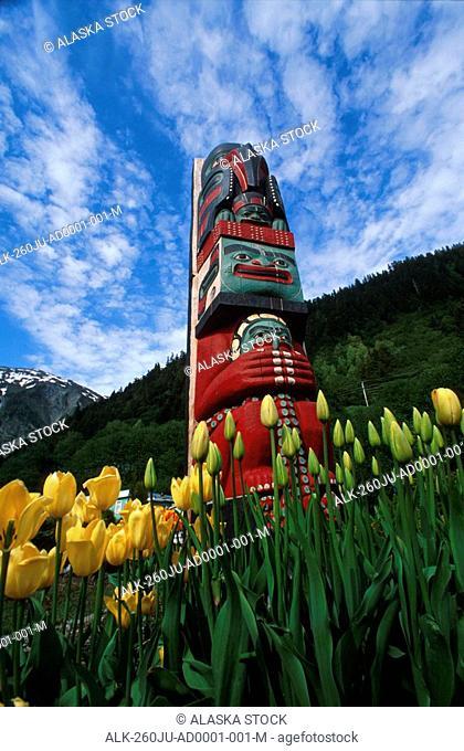 Totem pole with tulips Juneau Southeast Alaska mountains coast summer PR tourist