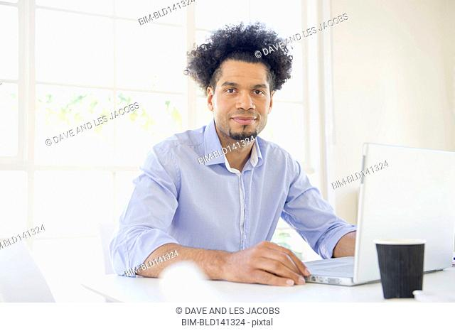 Mixed race businessman using laptop at conference table