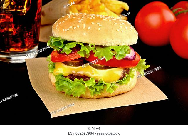 Menu- big cheeseburger with french fries and glass of cola on wooden black desk on black background