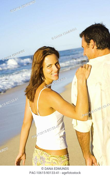 Hawaii, Oahu, North Shore, Happy couple walking on beach in warm afternoon light