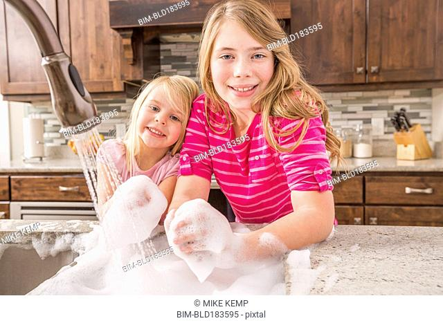 Caucasian girls washing hands in kitchen sink