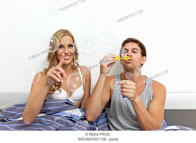 Young couple sitting in bed, blowing soap bubbles