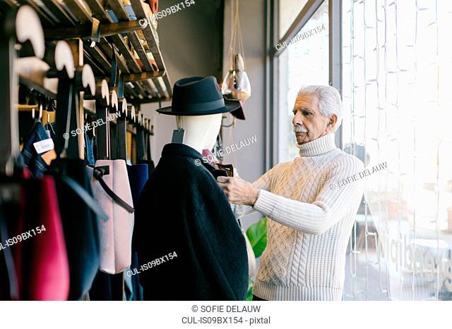 Senior man working in clothes shop
