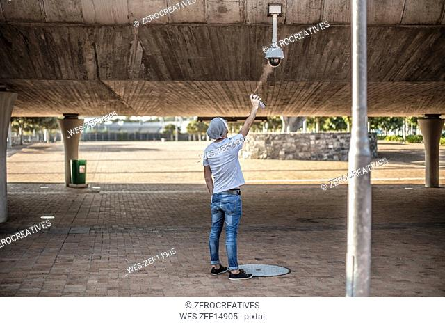 Man wearing a white mask spraing a security camera with spraypaint
