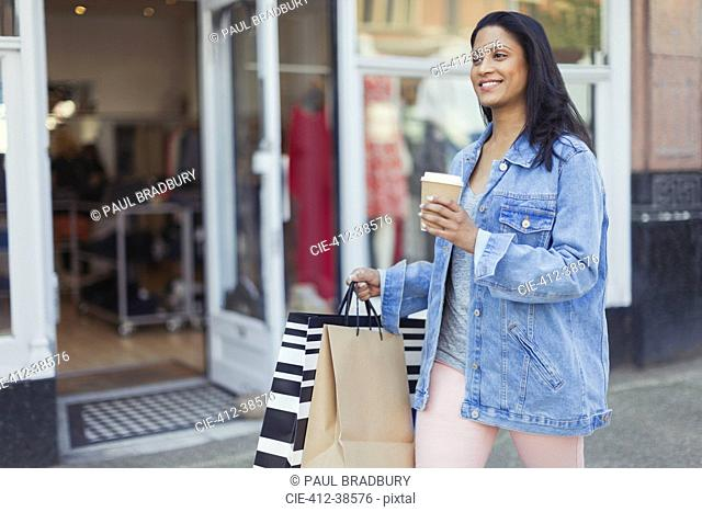 Smiling woman walking along storefront with coffee and shopping bags