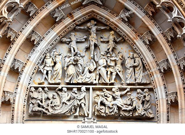 Tympanum Reliefs Above the Bronze Door of the central portal in the St. Vitus Cathedral's western facade, depicting The Crucifixion and a game of dice in order...