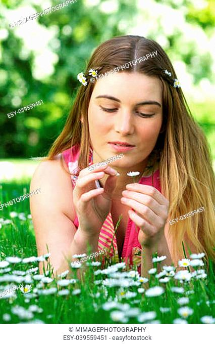 Portrait of a beautiful young woman sitting in the park picking flower petals