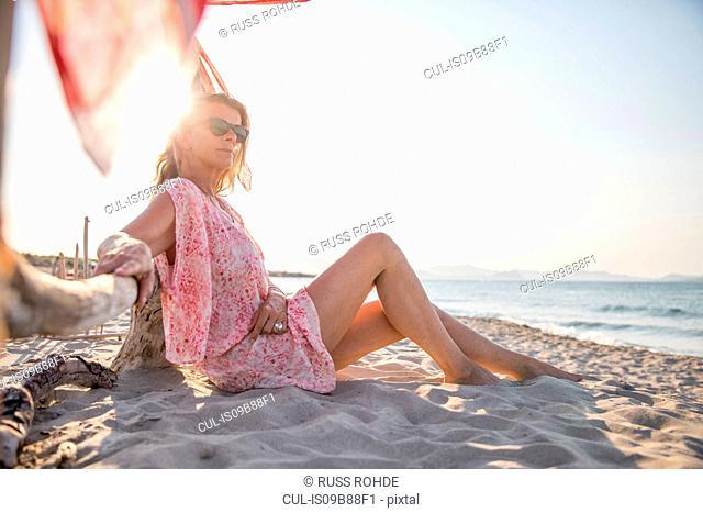 Woman sitting on beach relaxing, Palma de Mallorca, Islas Baleares, Spain, Europe