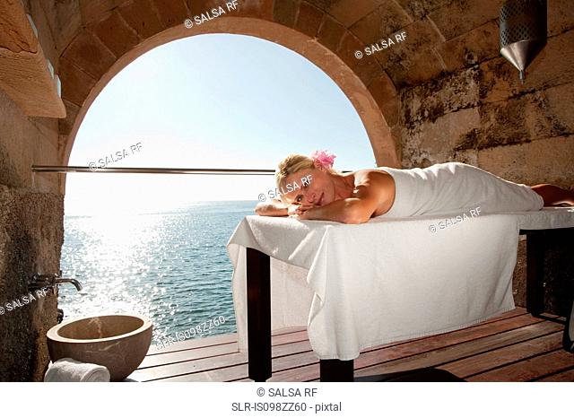 Woman lying on massage table by the ocean
