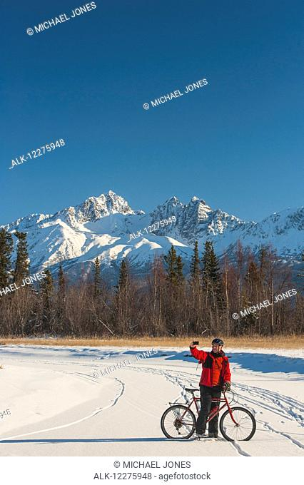 Man bicycling on frozen Rabbit Creek in the Palmer Haystack Game Refuge takes a selfie with Twin Peaks in the background, Southcentral Alaska, winter