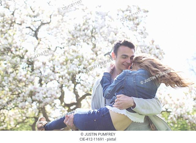 Man lifting woman under tree with white blossoms