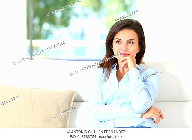 Front view of a pensive homeowner sitting on a couch in the living room at home