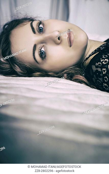 Beautiful young woman laying down in bed