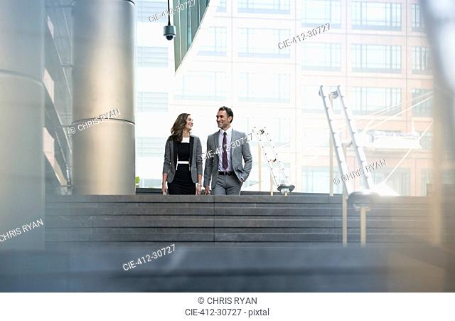 Corporate businessman and businesswoman descending stairs outdoors
