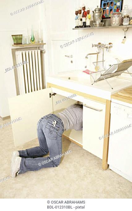 woman hidden in cupboard while repairing kitchen sink